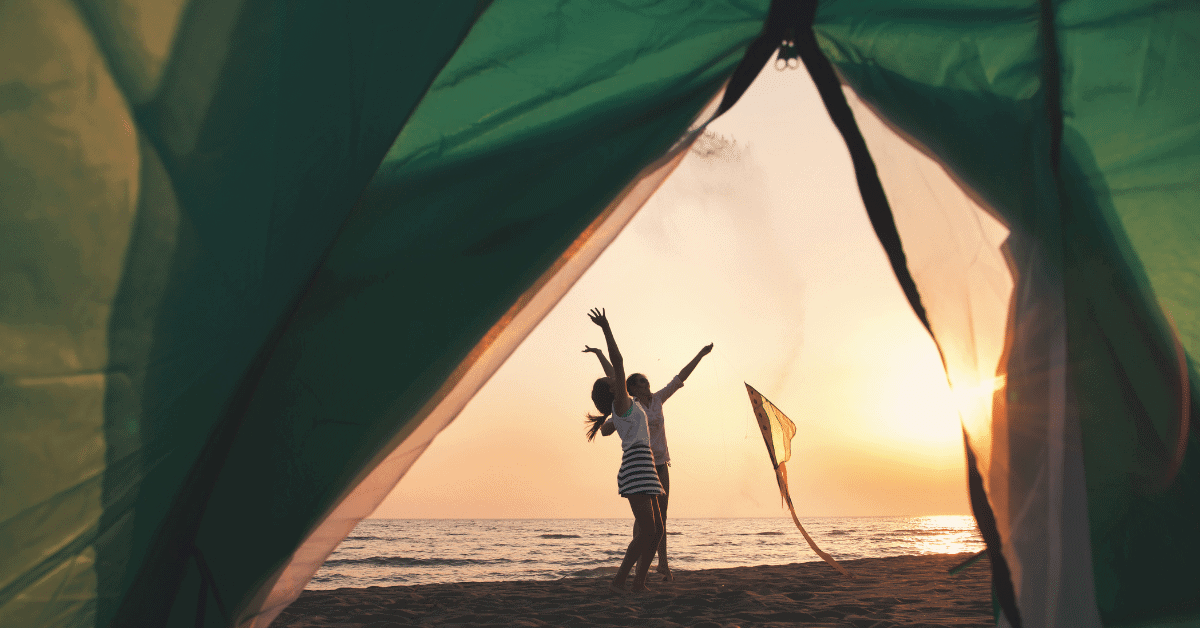 2 people on a beach in front of a tent