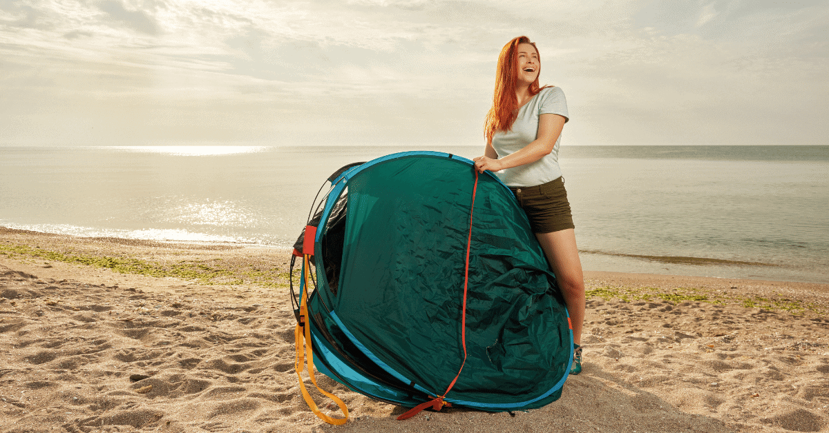 a woman on a beach holding a folded popup tent