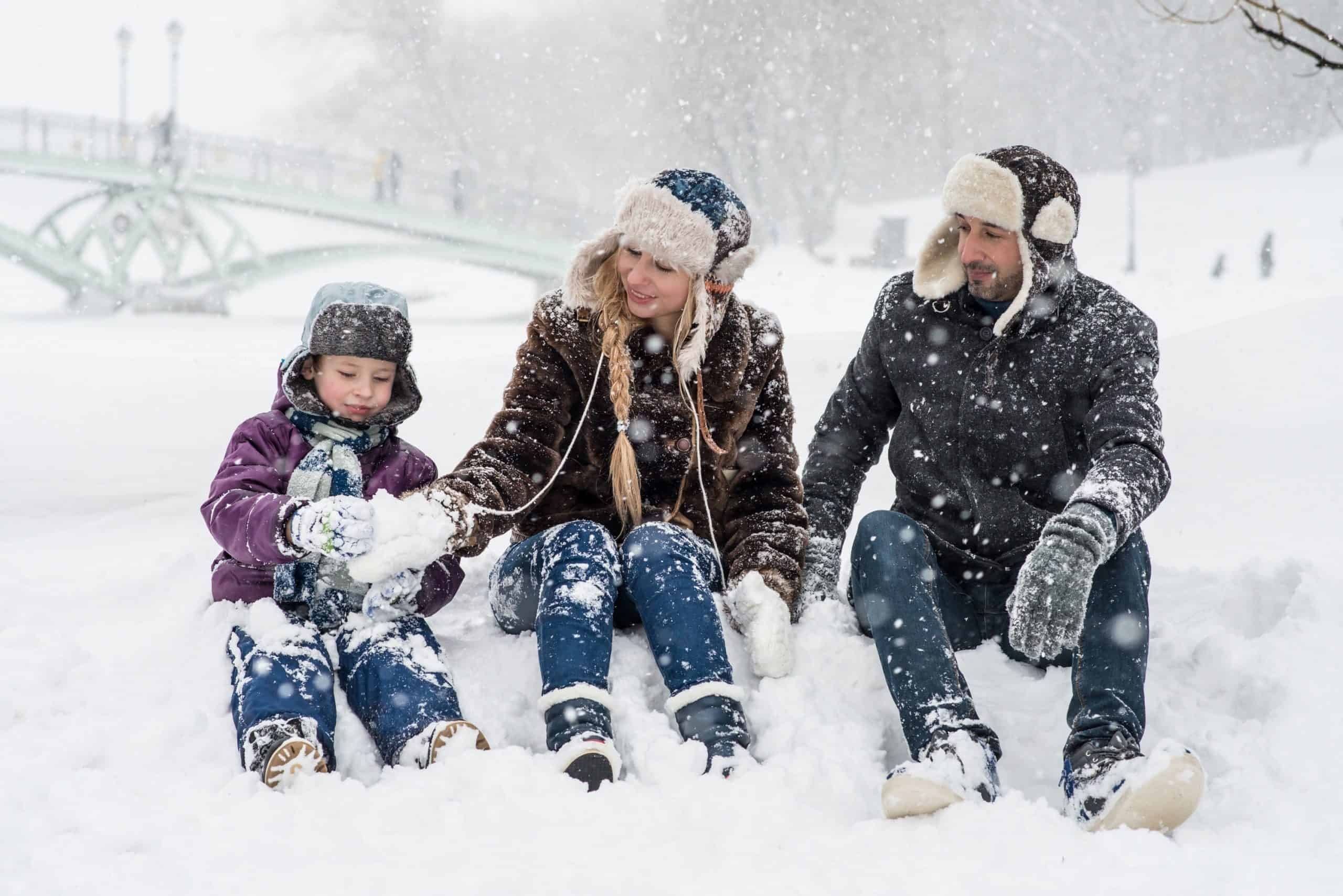 Woman, man, and girl sitting on snow