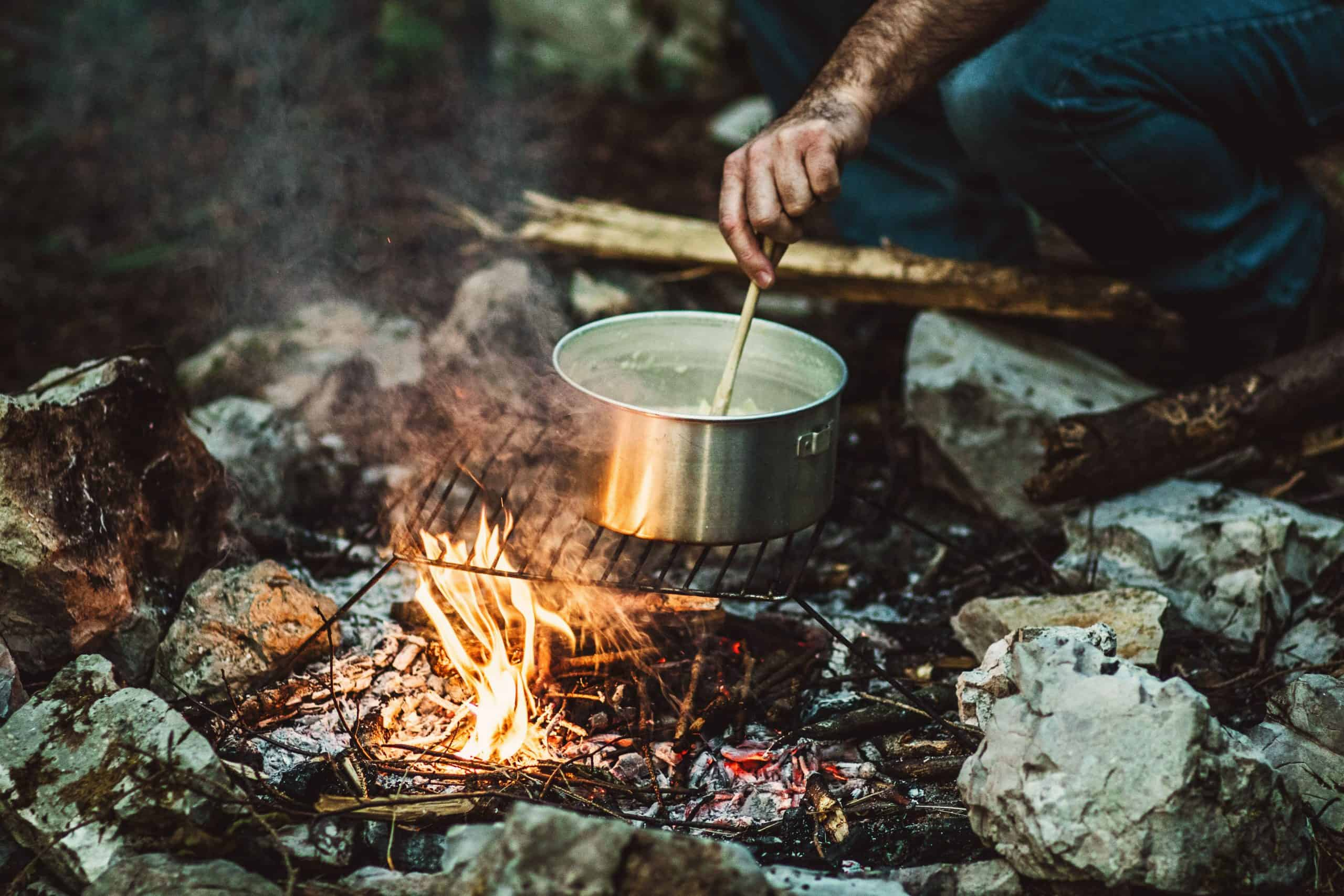 man cooking stew over the campfire