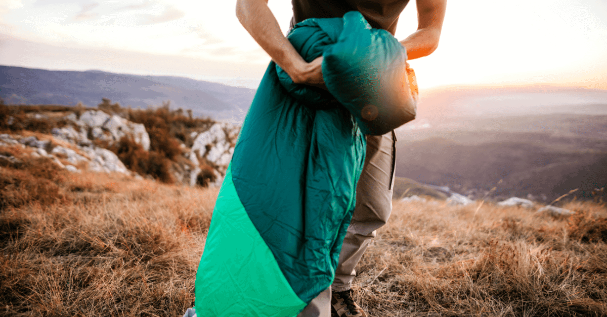 a person carrying a rectangular sleeping bag