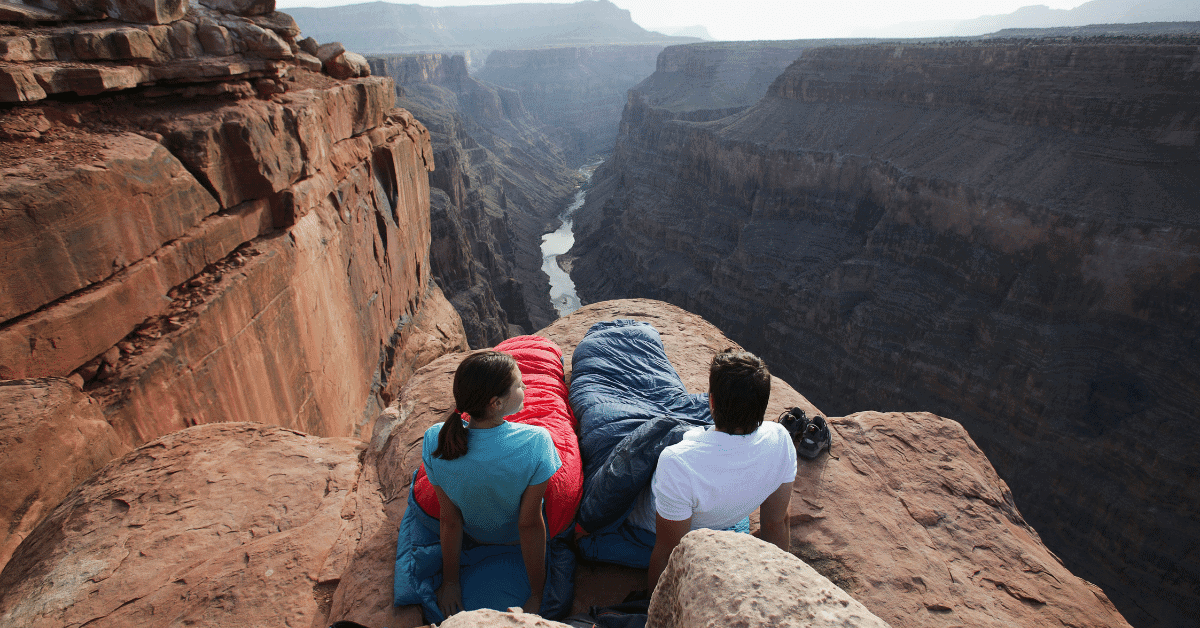 man and woman in sleeping bags overlooking canyon