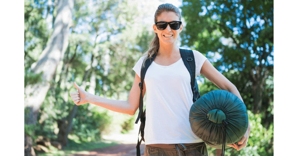 girl holding packed sleeping bag