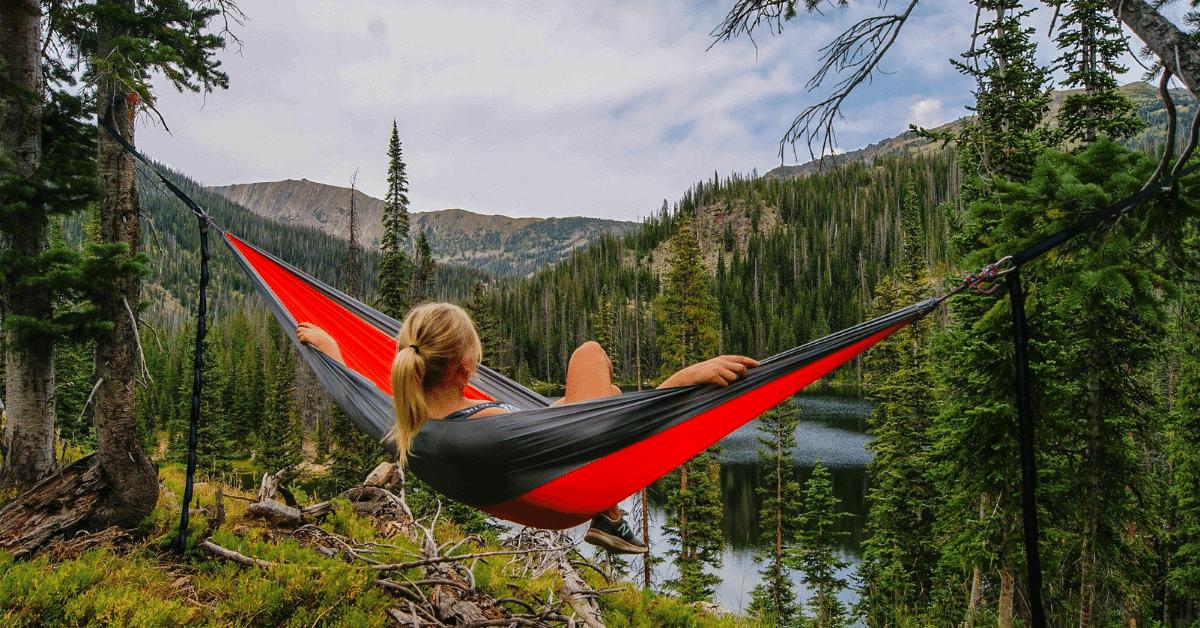 girl lying in hammock overlooking lake