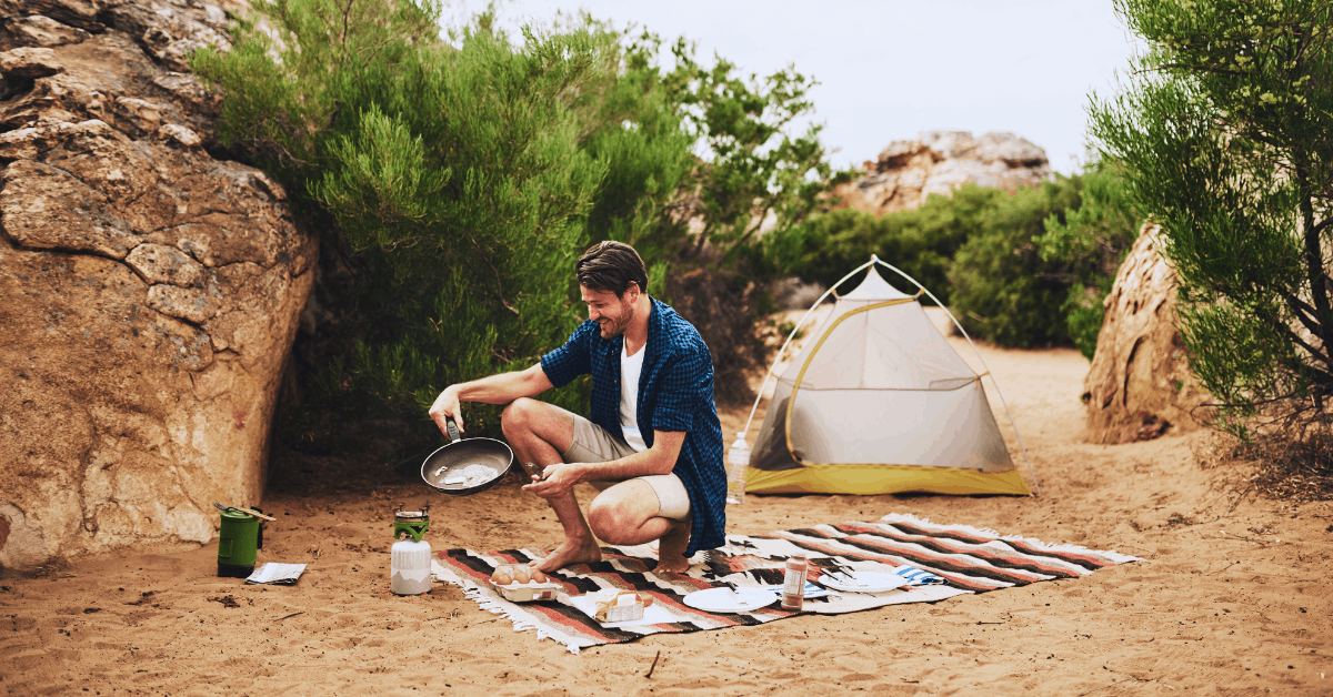 man cooking breakfast in front of tent