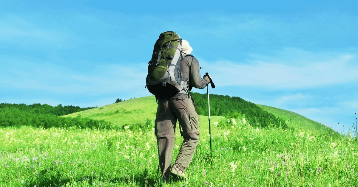 man hiking through field