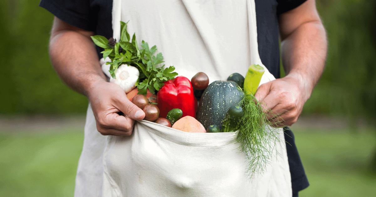 man holding apron full of vegetables