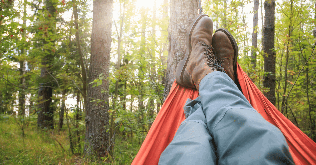 person lying in a hammock wearing boots