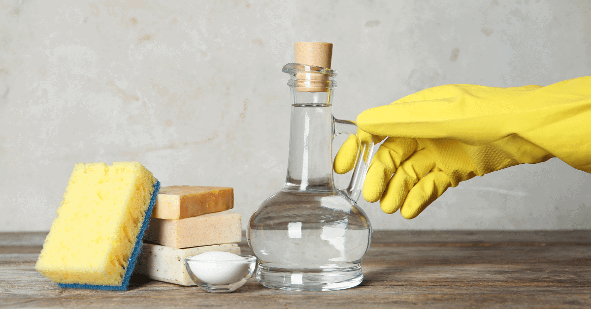rubber glove holding vinegar next to soap and spongerubber glove holding vinegar next to soap and sponge