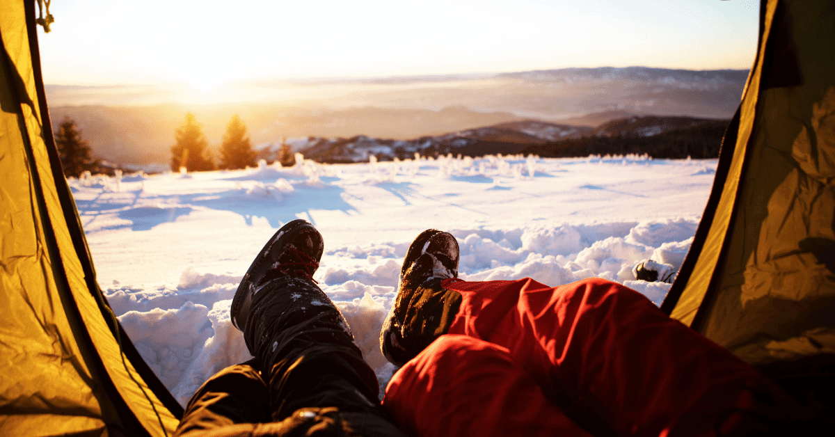 two people wearing snow boots in a tent