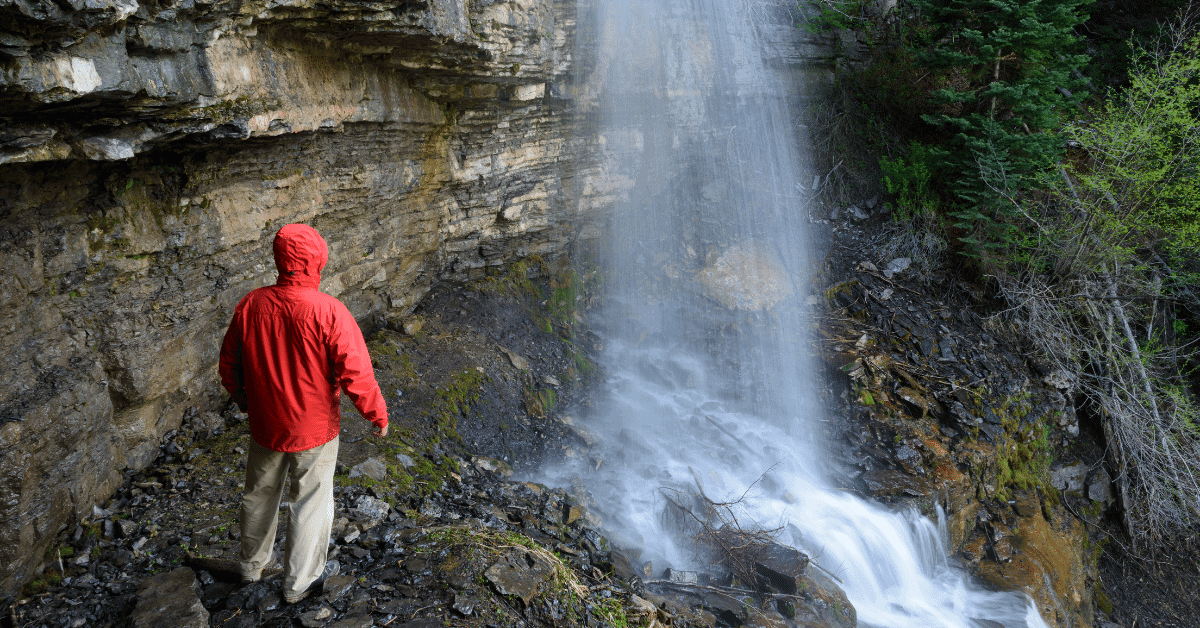a person wearing a rain jacket next to a waterfall