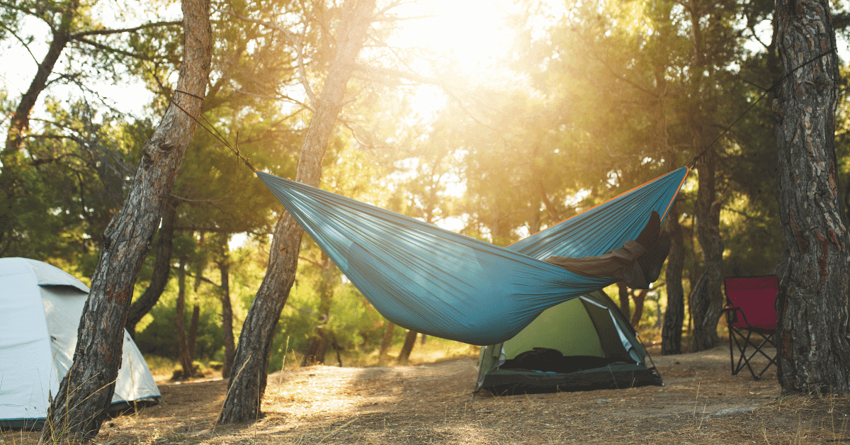 person in a hammock with tents in the background
