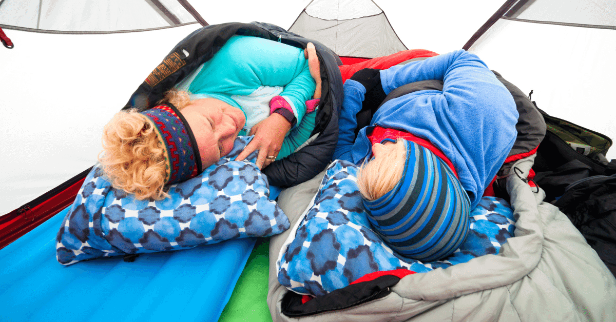 2 people in warm clothes and sleeping bags inside a tent