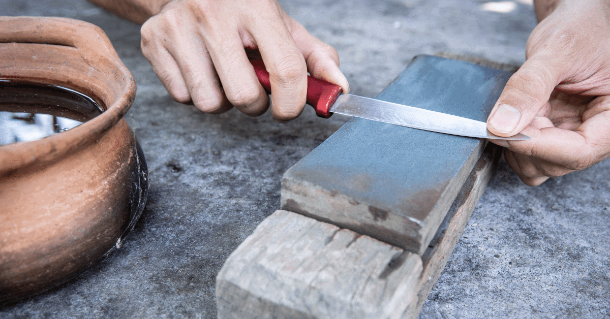 a person using a whetstone to sharpen a knife