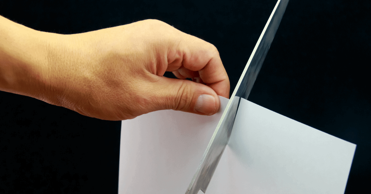 a person cutting paper with a knife to test sharpness