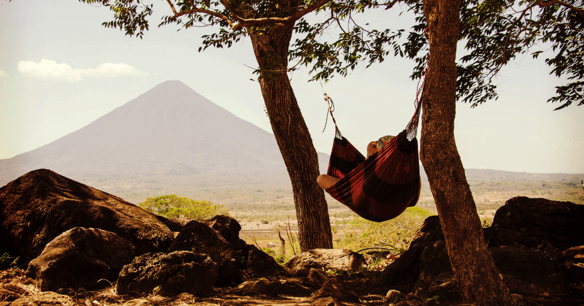 a person lying in a hammock with a volcano in the background