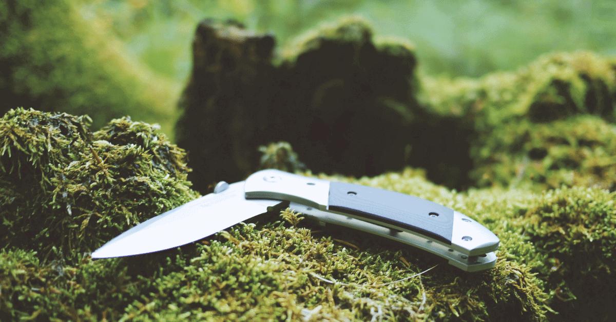a pocket knife on a mossy surface