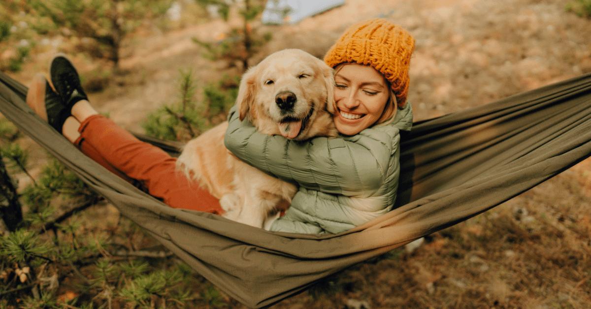 a woman and a dog in a hammock cuddling