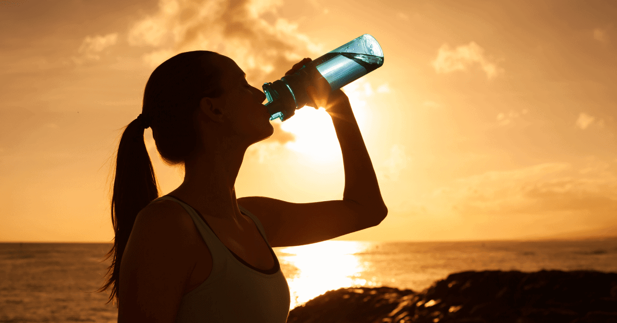 a woman drinking water from a bottle