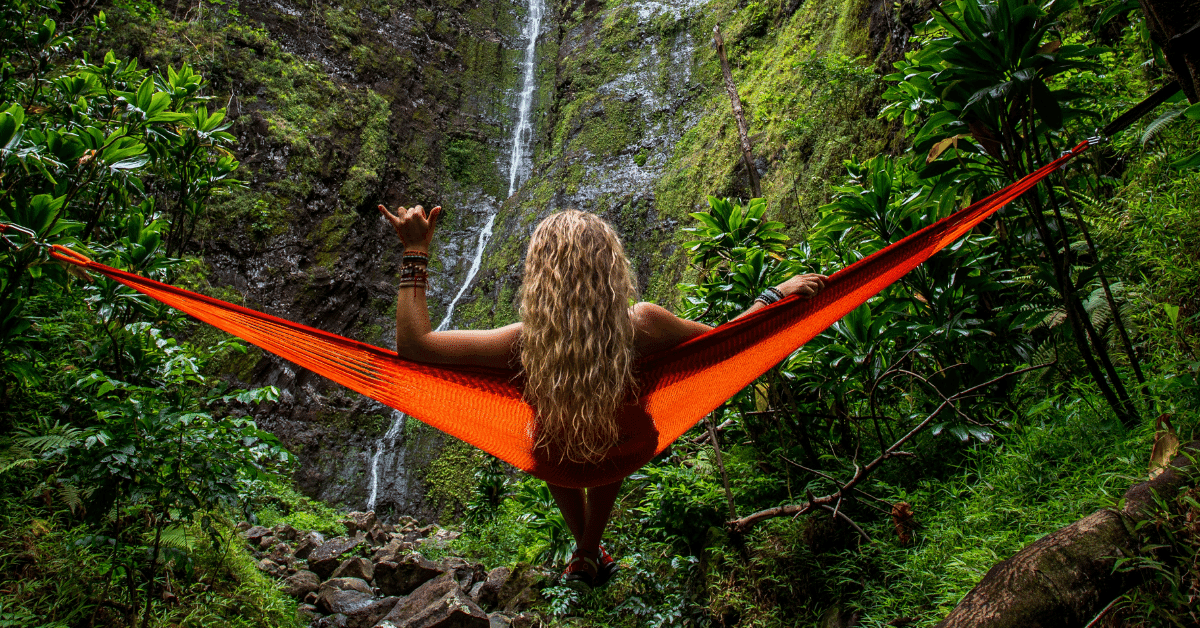 a woman sitting in a hammock in front of a waterfall