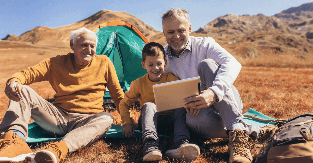3 generations sitting in front of a tent looking at a tablet