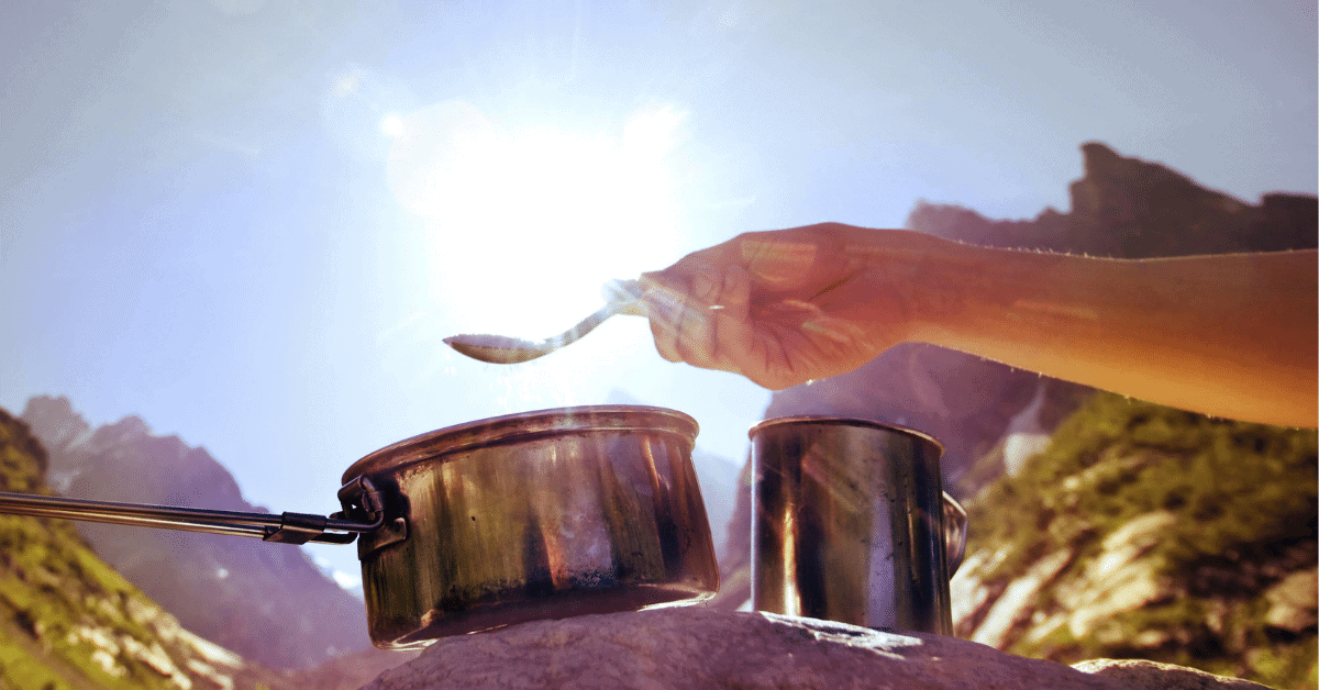 a cooking pot and a person holding a spoon with mountains in the background