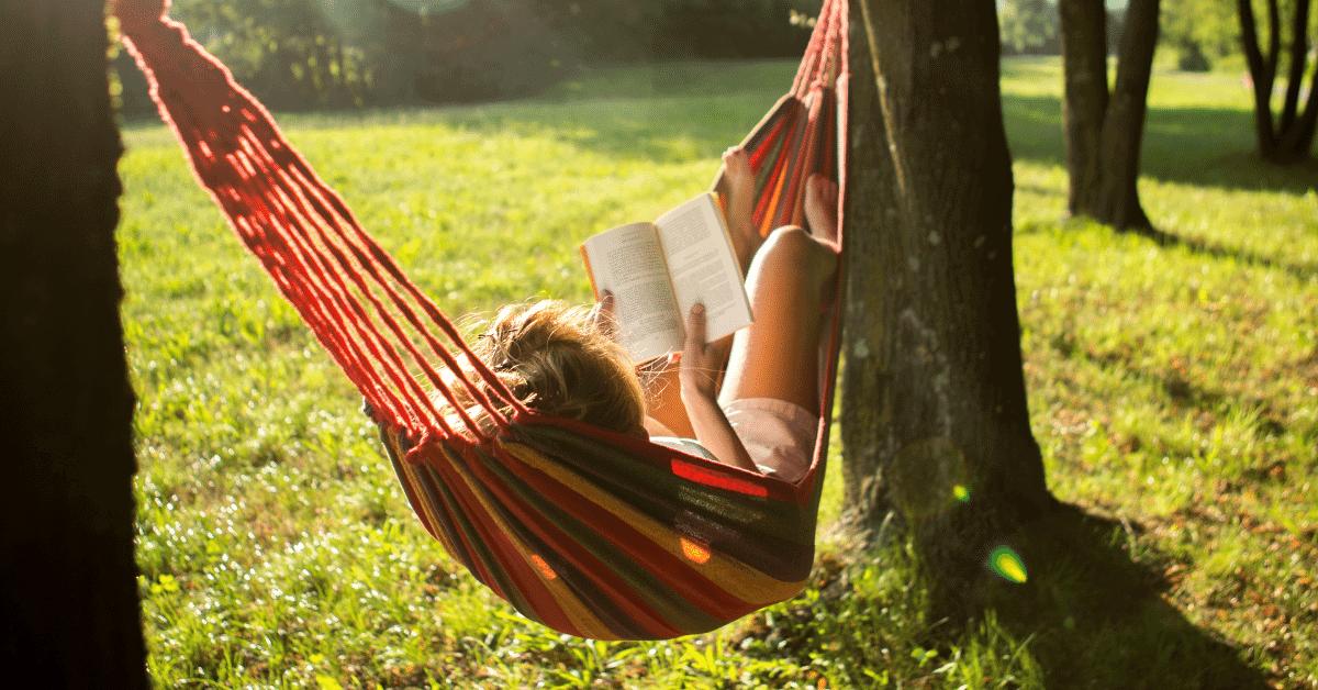 a girl lying in a hammock reading a book