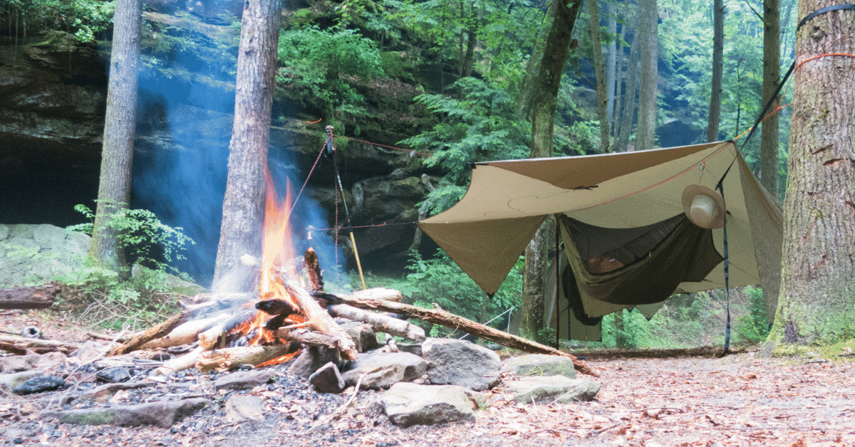 a hammock with a bug net and hammock tarp over it