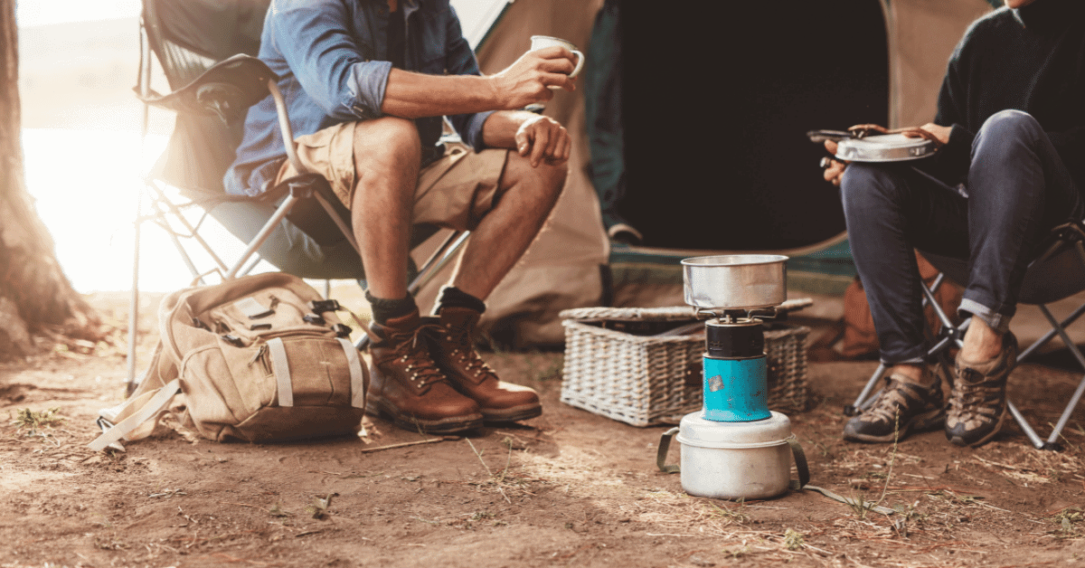 a man and woman sitting at a campsite