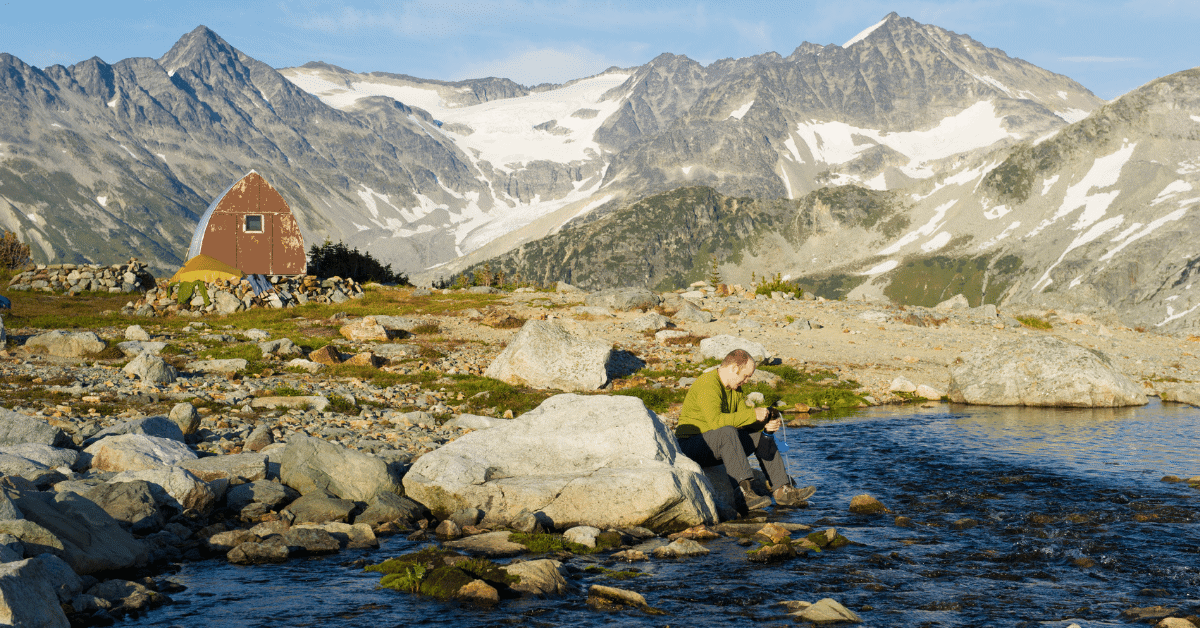 a man filtering water from a stream in the mountains