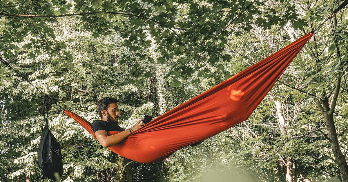 a man laying in a hammock between trees