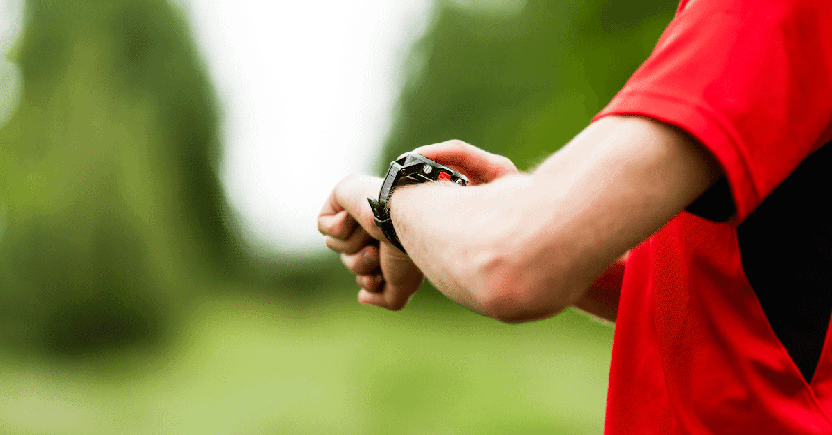a man looking at a hiking watch
