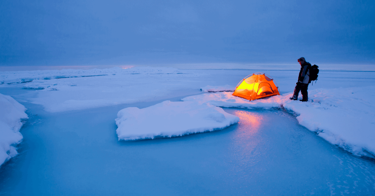 a man next to a tent in an arctic landscape