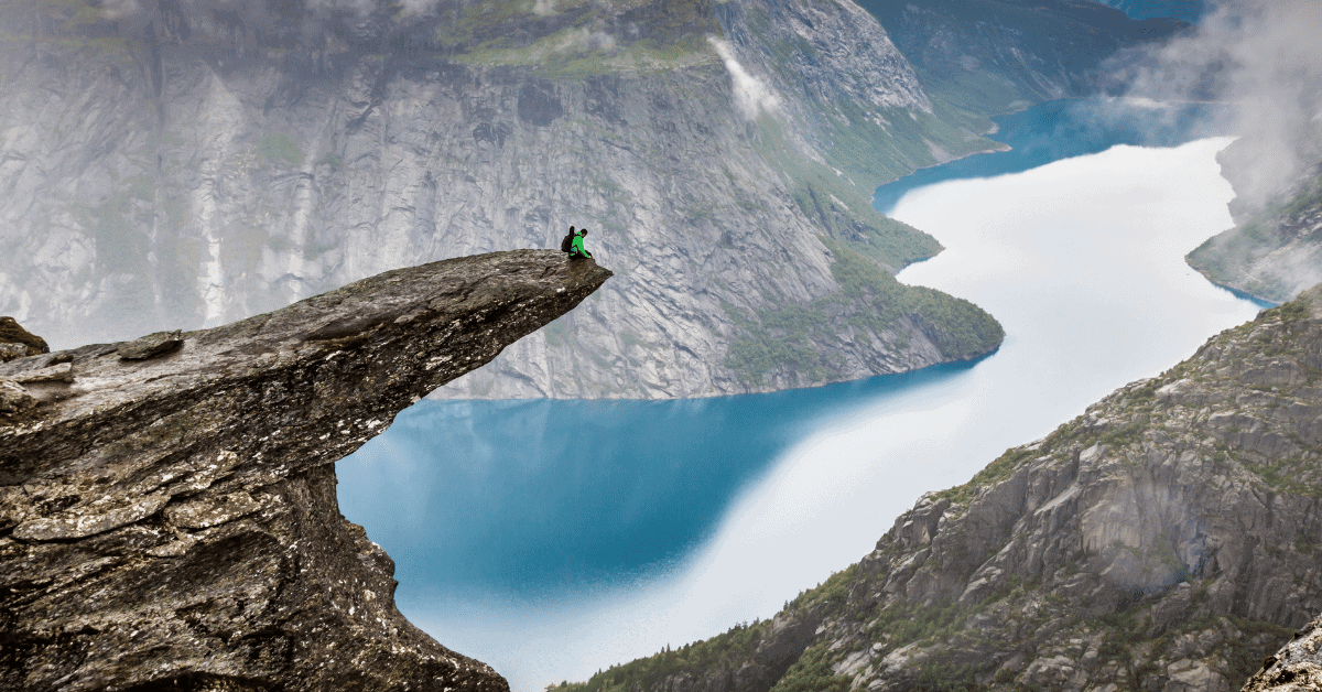 a man sitting on the edge of a cliff over a lake