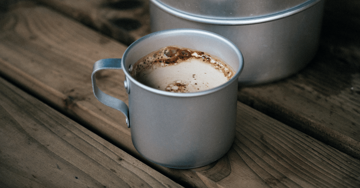 a metal mug of coffee on a wooden table