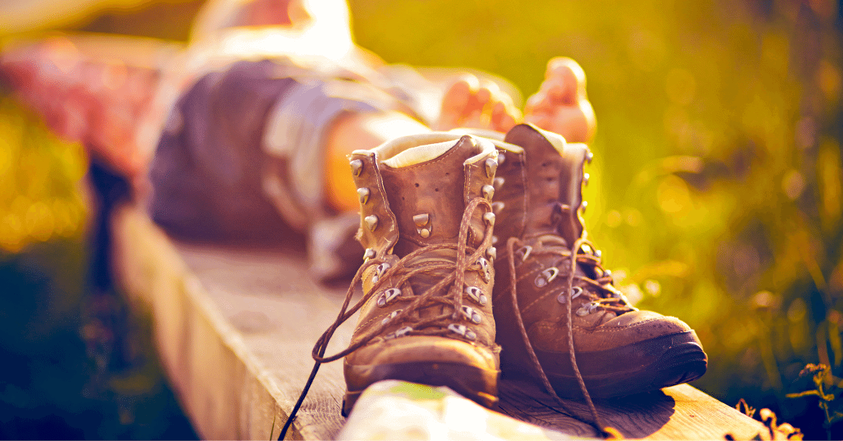 a pair of hiking boots with a barefoot hiker relaxing in the background