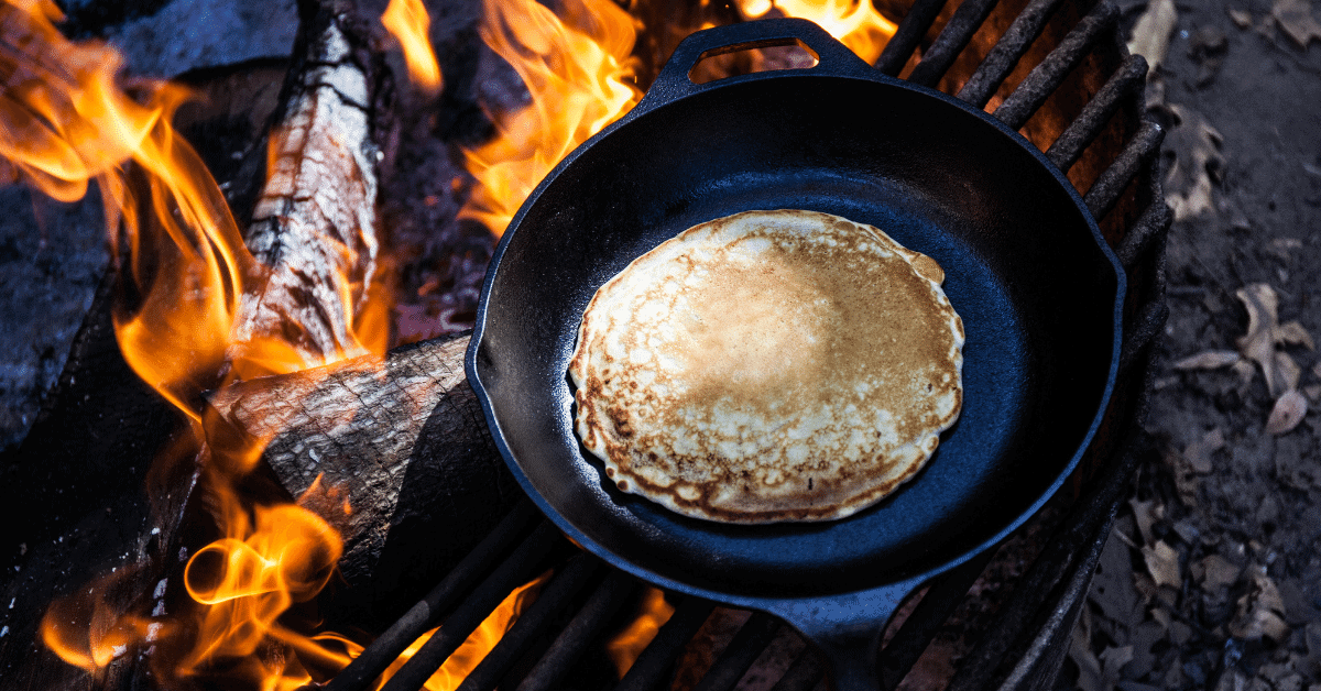 a pancake cooking on a campfire