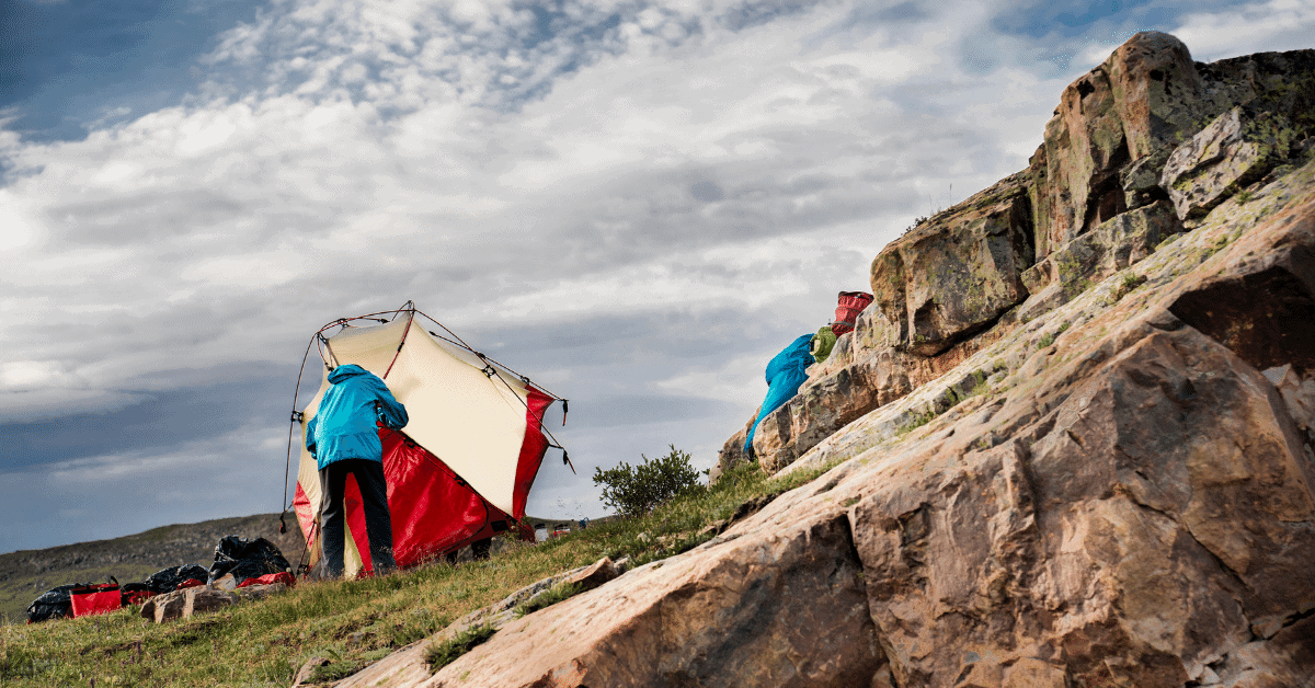 a person setting up a tent in windy weather