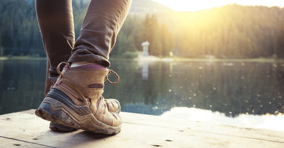 a person wearing hiking boots next to a lake