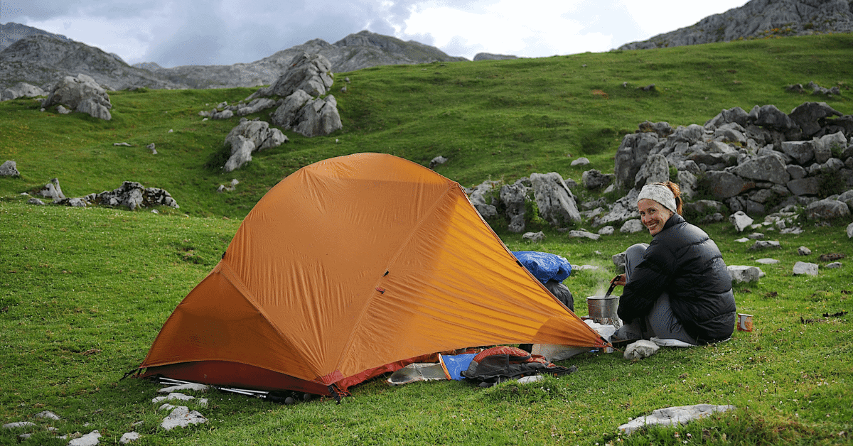 a woman cooking in front of a tent in the mountains