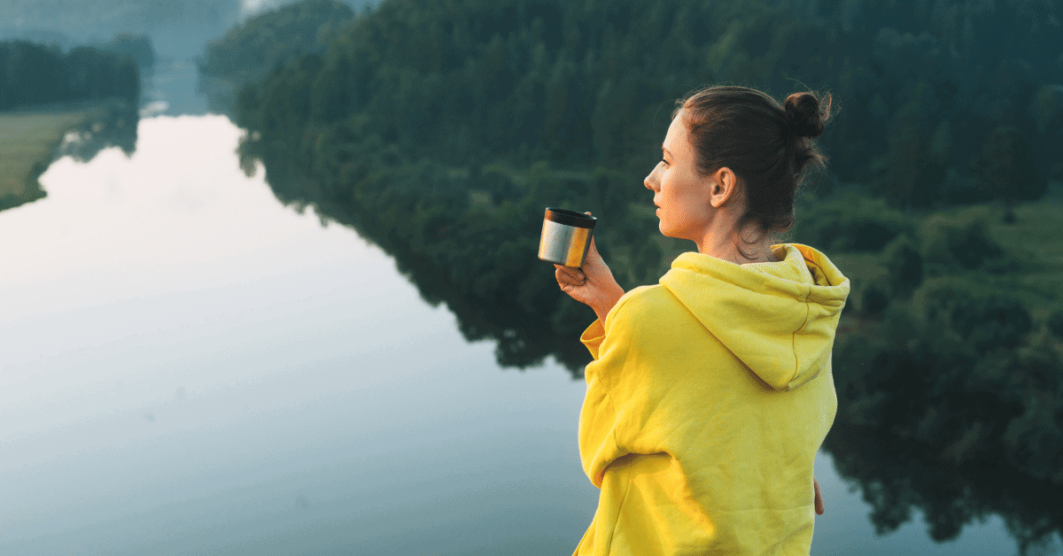 a woman drinking coffee by a river