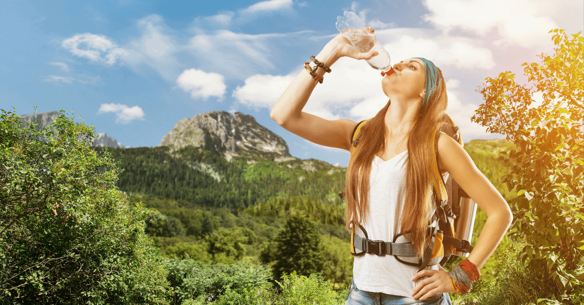 a woman drinking water from a bottle on a hike