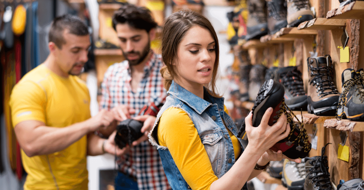a woman looking at hiking boots in a store