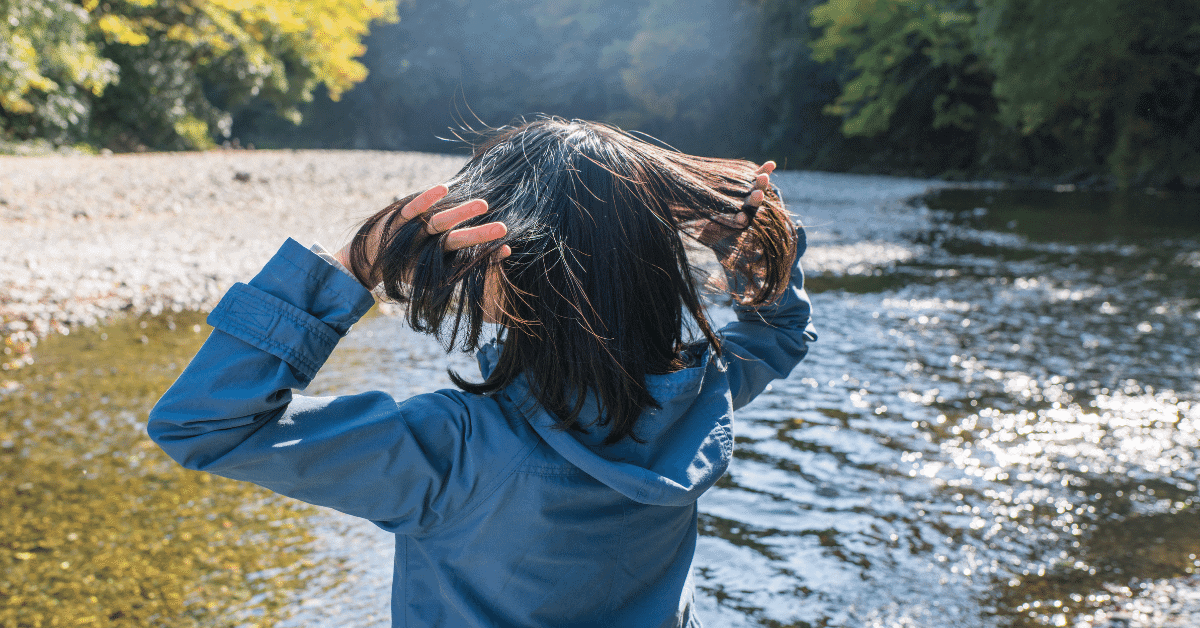 a woman running her fingers through her hair by a stream