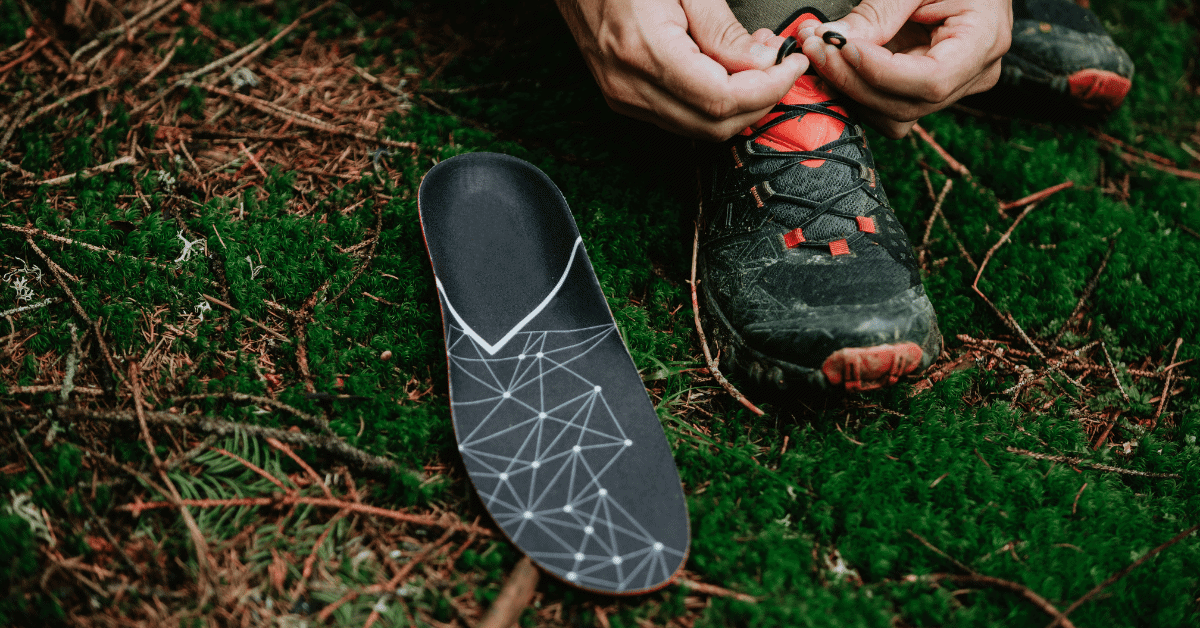 an orthotic on the grass next to a person tying the laces on their hiking shoes