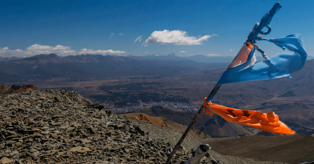 flags blowing in the wind on top of a mountain