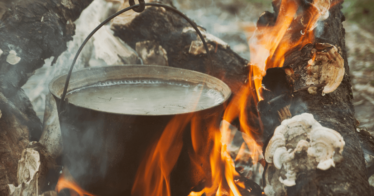 water boiling in a pot over a campfire