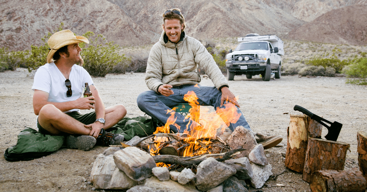 2 friends truck camping sitting around a campfire