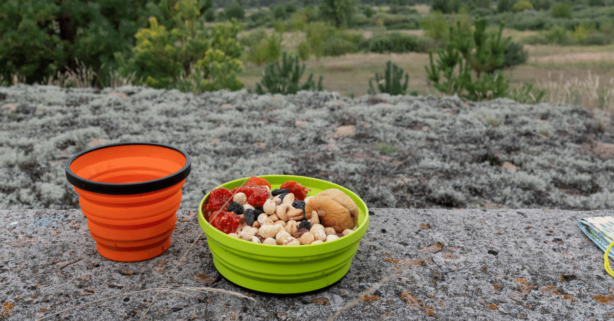 a bowl of fruit and nuts and a drinking cup