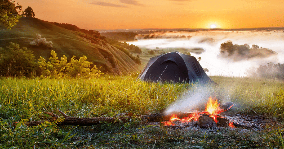 a campfire next to a tent in the hills